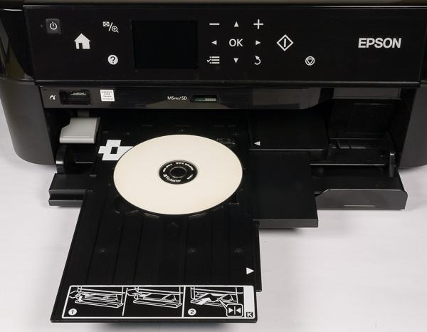 Загрузка оптического диска в тракт печатающего механизма осуществляется со стороны приемного лотка