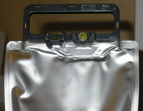 На пластиковой рамке в верхней части емкости расположен клапан для подсоединения к системе подачи чернил печатающего устройства и миниатюрная печатная плата с чипом