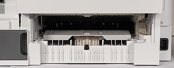 Нижняя часть задней панели МФУ со снятым модулем двусторонней печати. Темный серый блок слева — емкость для сбора отработанных чернил